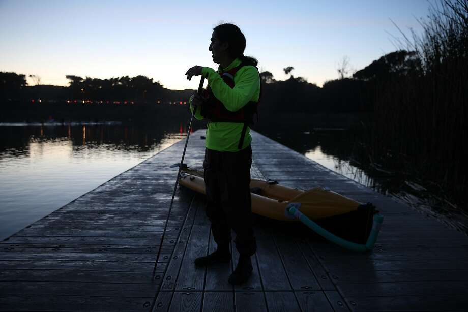 Ahmet Ustunel holds his navigation stick next to his kayak at Lake Merced in San Francisco. Photo: Santiago Mejia, The Chronicle