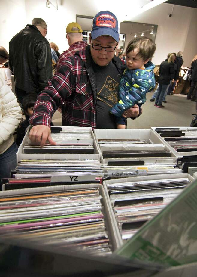 Doug Eng, of Trumbull, looks through boxes of records as he holds his son Arlan, 1, during WPKN's MUSIC MASH Record Fair 2018 at Read's Artspace building on Broad Street in Bridgeport, Conn., on Saturday, Mar. 3, 2018. MUSIC MASH 2018 featured 50+ vendors from all over New England selling vinyl LP's, 45's, CD's and music collectibles. Photo: Christian Abraham / Hearst Connecticut Media / Connecticut Post