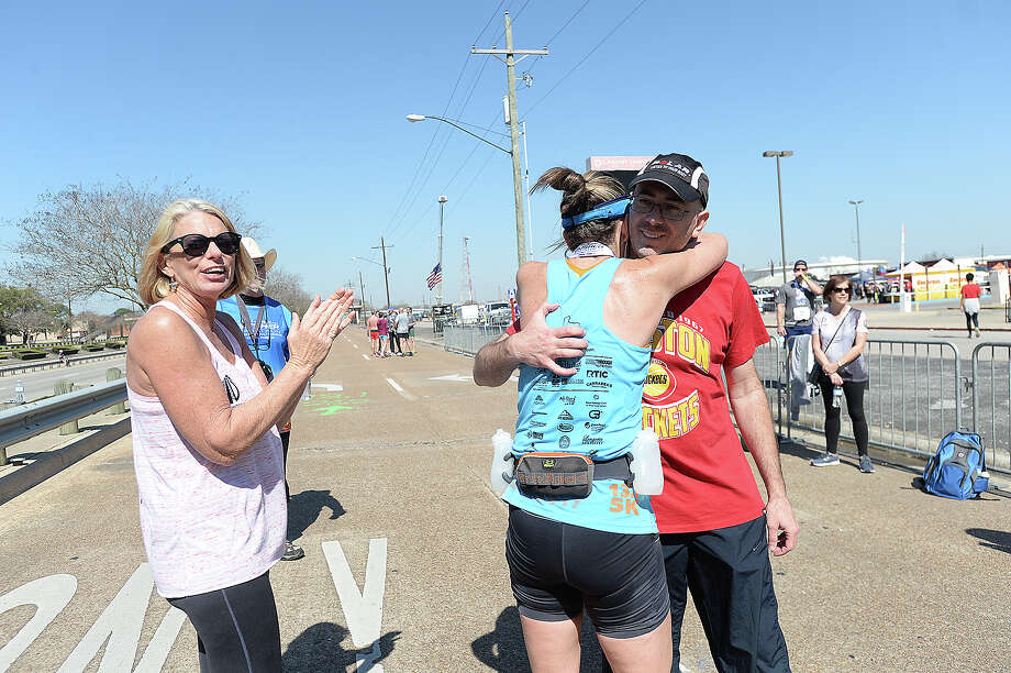 Jennifer Laughlin hugs her husband Clark after being first in the women's field to finish the full marathon as volunteer Cyndie Campbell applauds her during the Gusher Marathon, Half Marathon and 5K through Beaumont Saturday. Photo taken Saturday, March 3, 2018 Kim Brent/The Enterprise Photo: Kim Brent / BEN