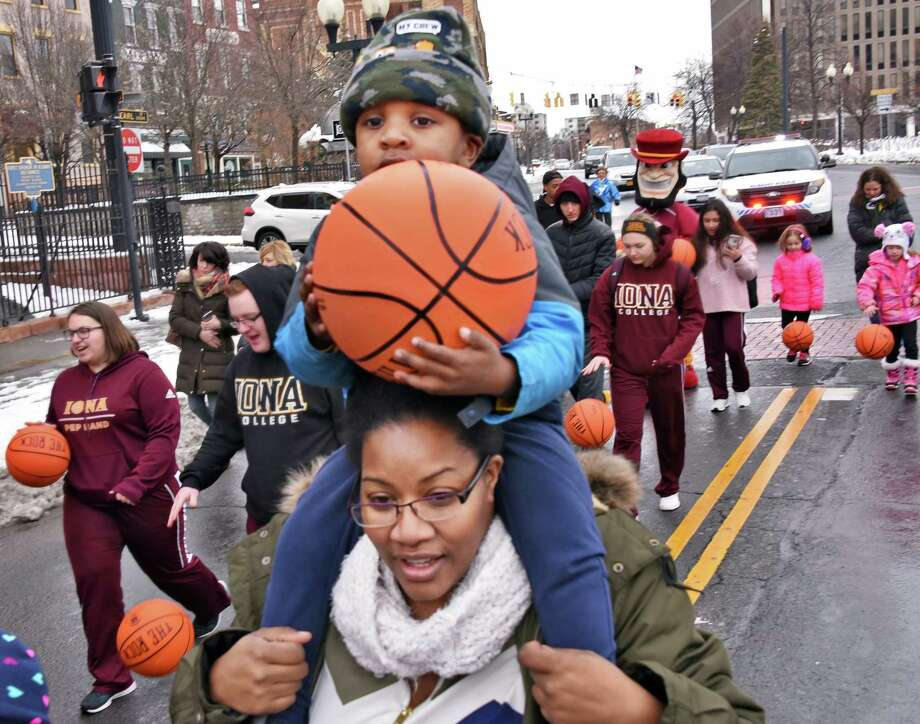 Three-year-old Spencer Stewart gets a lift from his mom, Asye Stewart of Pemberton, NJ, as children dribble basketballs from the Palace Theatre to the Times Union Center during the Bounce to the Arena celebrating the return of the MAAC Championships Saturday March 3, 2018 in Albany, NY.  (John Carl D'Annibale/Times Union) Photo: John Carl D'Annibale / 20043110A