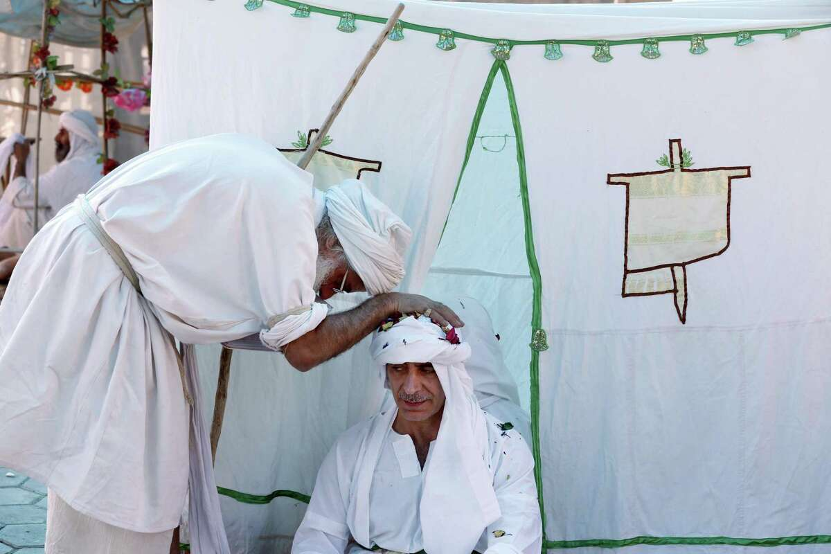 A Sabean Mandaean cleric prays for a groom during a mass wedding near the banks of the Tigris River in Baghdad, Iraq, Sunday, March 6, 2016. The Sabean Mandaean community is a pre-Christian sect that follows the teachings of John the Baptist. Many fled the country or were killed following attacks by Muslim extremists after the 2003 ouster of Saddam Hussein. (AP Photo/Karim Kadim)