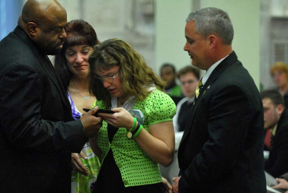 UAlbany's University Police Department (UPD)Chief J. Frank Wiley, left,  presents James and Lisa  Bailey and their daughter Katie, second from right, with an official UPD badge in honor of their late son Richard Bailey, a UAlbany senior who was murdered in October 2008, during a Memorial Mass to celebrate his life in Albany, NY  Thursday March 26, 2009. Bailey had already earned his Bachelor of Arts degree in Sociology with a Minor in Criminal Justice, and would have graduated in December. He wanted to become a police officer. (Philip Kamrass /  Times Union) Photo: PHILIP KAMRASS / 00003048A