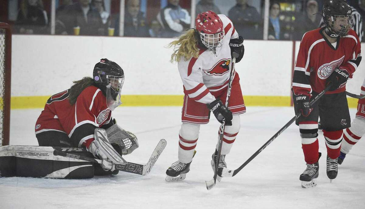 Greenwich's Riley Ellsworth, center, looks to pass in the crease against Branford goalie Julia SanGiovani during a CIAC quarterfinal game at the Dorothy Hamill Skating Rink on Saturday in Greenwich.