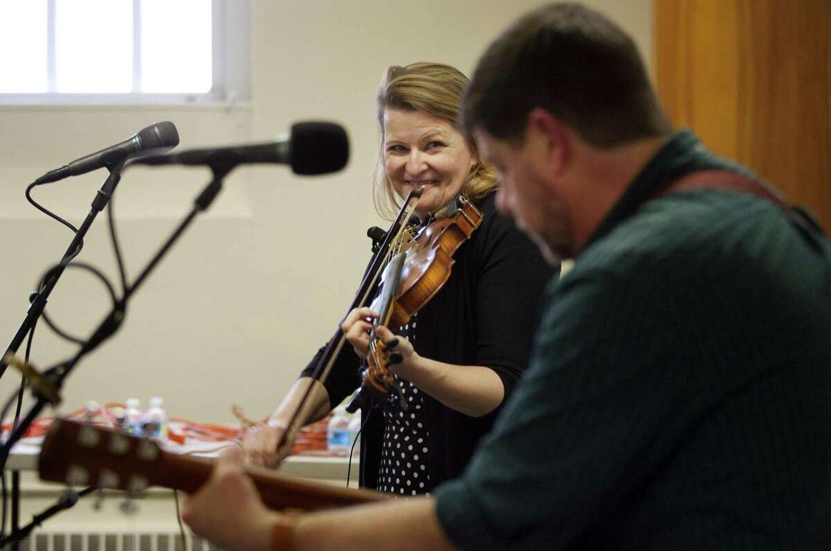 Traditional Irish fiddler Deirdre McMorrow, smiling, and guitarist/vocalist Paul Pender, perform together during a free concert at the Seymour Public Library in Seymour, Conn., on Saturday, Mar. 3, 2018. Funding for this concert was provided through a grant from the Matthies Foundation.