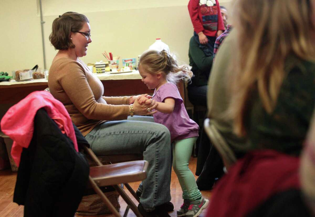 Ariella Perez, 3, of Seymour, dances to the music of traditional Irish fiddler Deirdre McMorrow and guitarist/vocalist Paul Pender during a free concert at the Seymour Public Library in Seymour, Conn., on Saturday, Mar. 3, 2018. At left is Ariella's mom Martina. Funding for this concert was provided through a grant from the Matthies Foundation.