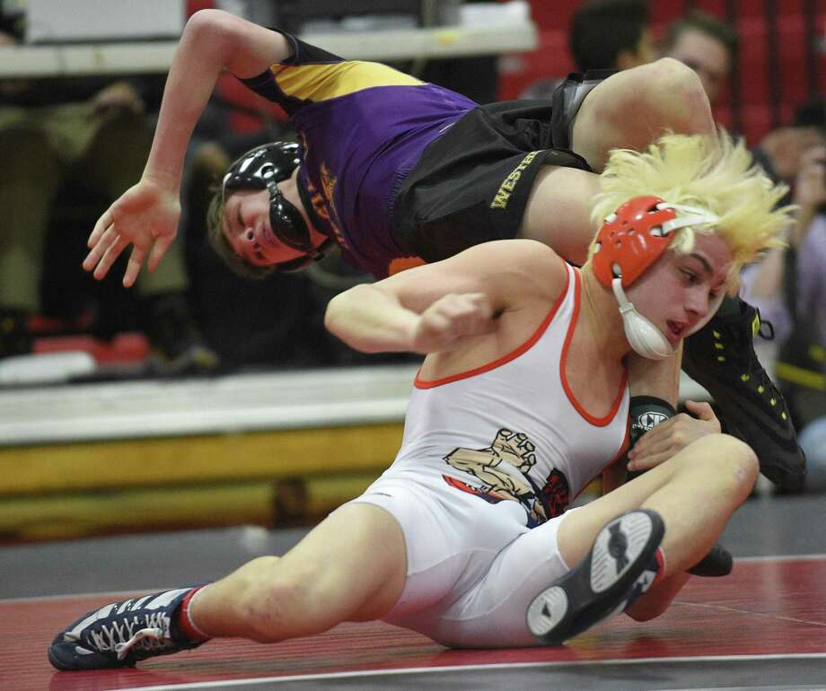 Danbury Ryan Jack (white) wrestles Westhill's Chase Parrott (purple) in the 120 pound match of the FCIAC Boys Wrestling Championship finals at New Canaan High School  in New Canaan, Conn. on Saturday, Feb. 10, 2018. Jack defeated Parrott 4-3. Photo: Matthew Brown / Hearst Connecticut Media / Stamford Advocate