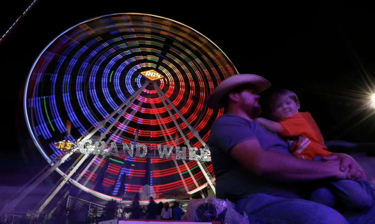 Paul Harris and his son, Tyson, 3, of Missouri City, wait next to the Grand Wheel on the midway at the Houston Livestock Show and Rodeo at NRG Park, Saturday, March 3, 2018, in Houston.