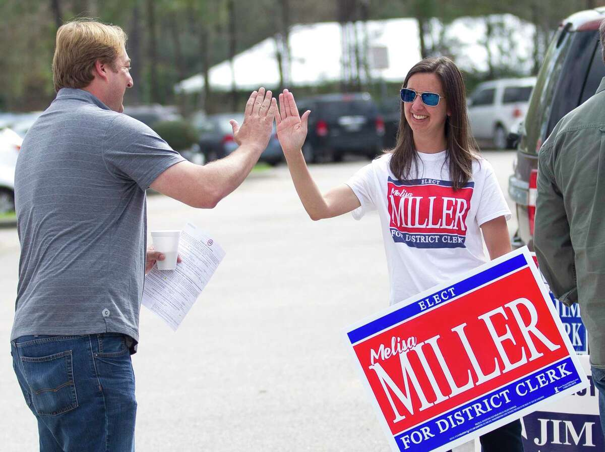 Melisa Miller, candidate for Montgomery County district clerk, gets a high-five during the last day of early voting at the South County Community Center, Friday, March, 2, 2018, in The Woodlands.
