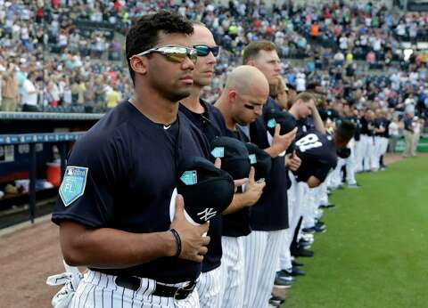 4dca514df0d3f Seattle Seahawks quarterback Russell Wilson stands with New York Yankees  players for the national anthem before