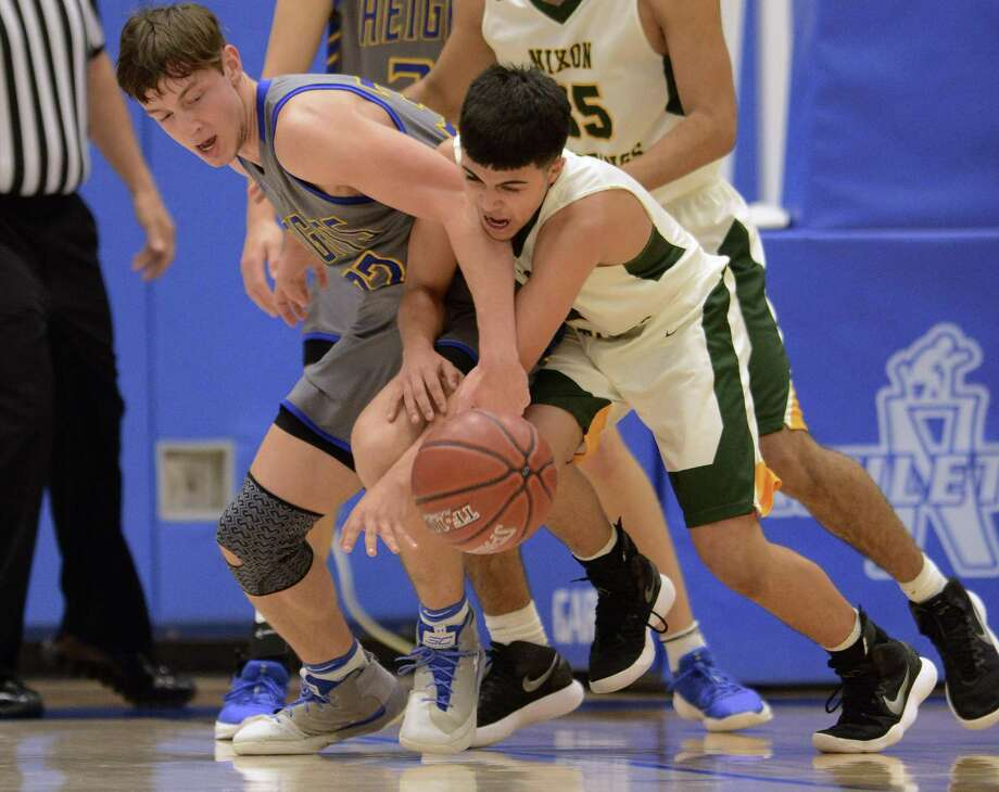 Andrew Reichert of Alamo Heights, left, and Jose Herrera of Laredo Nixon battle for a loose ball during UIL Region IV-5A boys basketballl finals at the Northside ISD Gym on Saturday, March 3, 2018. Alamo Heights won, 70-33. Photo: Billy Calzada, Staff / San Antonio Express-News / San Antonio Express-News