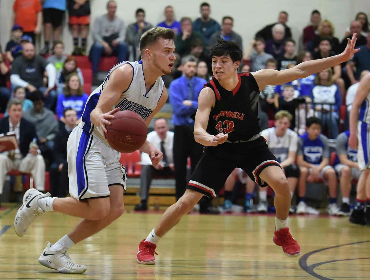 East Hampton's senior guard Thomas Close drives to the hoop past Cromwell senior guard Reese Reyes, Saturday, March 3, 2018, in the Shoreline championship game at the Salisbury Gymnasium at Wilbur Cross High School in New Haven. East Hampton won, 58 - 54.