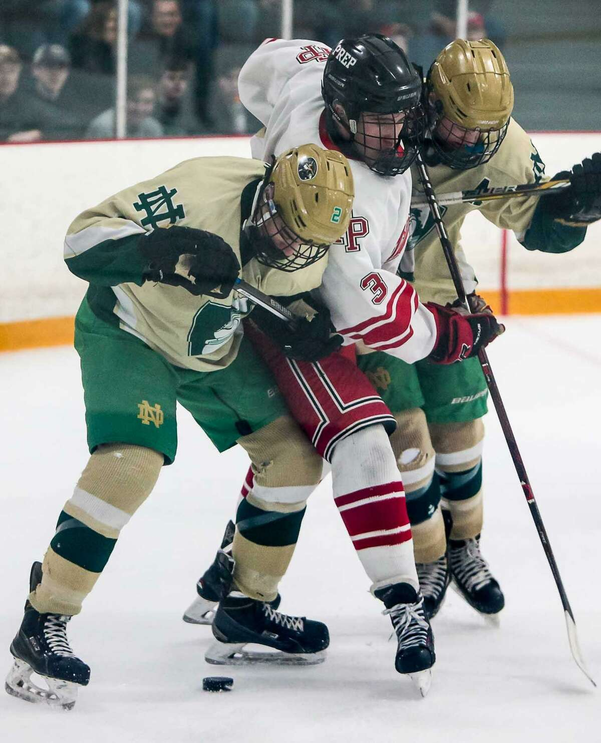Fairfield Prep's Skler Celotto battles for the puck against Notre Dame's Kevin Millea(2) and Clayton Coasin (6) during the SCC-SWC Division I championship game Saturday in West Haven.