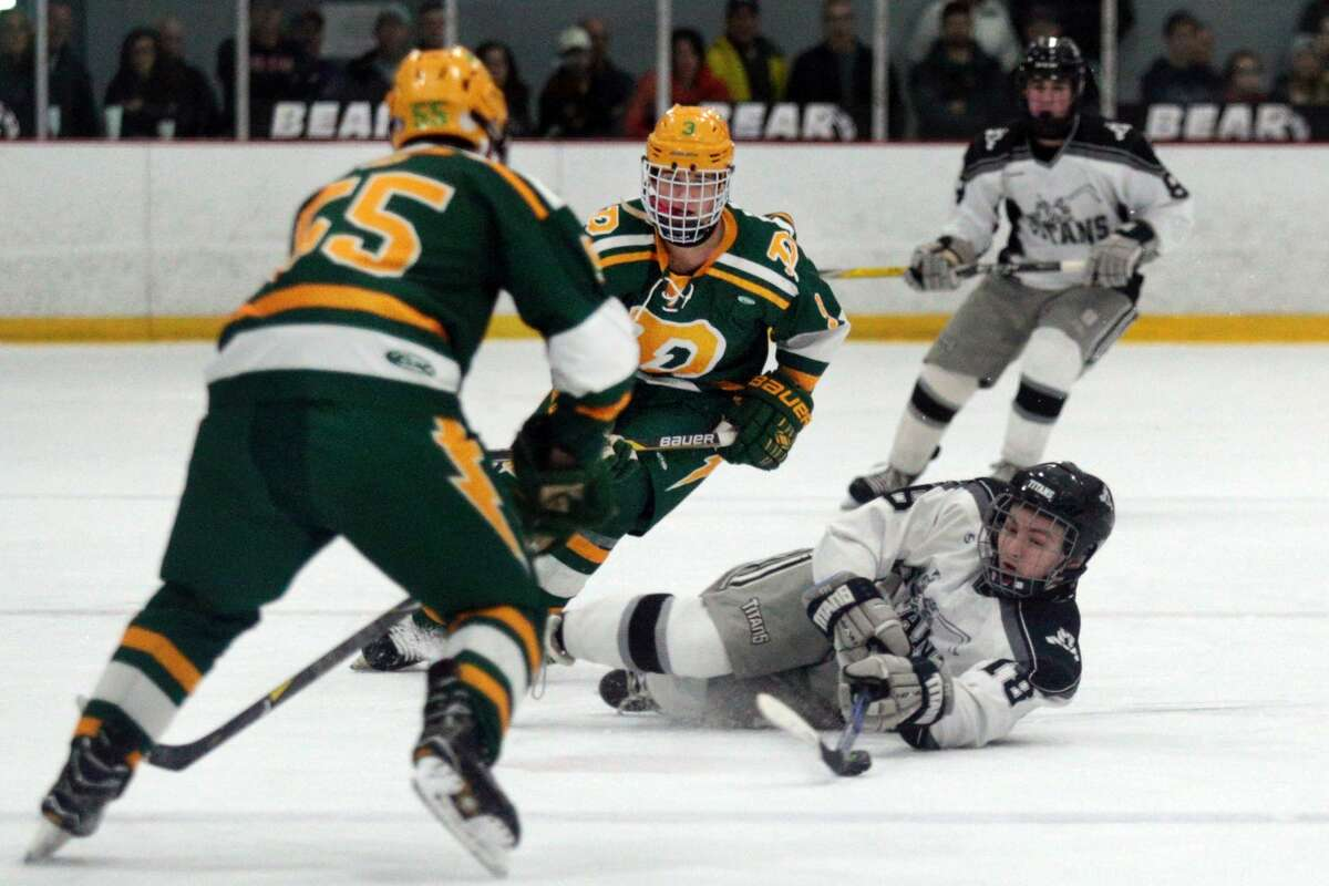 Tri-Valley's Jacob Shinaver (18) attempts to pass the puck from the ground while Dow's Garrett Brillhart skates alongside him during their game at Midland Civic Arena on Saturday, March 3, 2018. (Samantha Madar/for the Daily News)