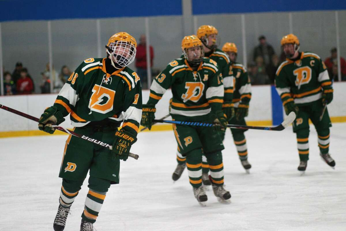 Dow players head to their teammates to celebrate after scoring during a game against Tri-Valley at Midland Civic Arena on Saturday, March 3, 2018. (Samantha Madar/for the Daily News)