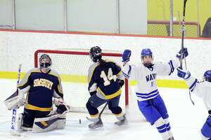 Darien's Shea van den Broek, right, reacts after beating Simsbury goalie Tori LaCroix, left, scoring the first goal of the game for Darien in the first period of the girls high school state hockey playoff game between Darien High School and Simsbury High School at Terry Conners Ice Rink in Stamford, Conn., Saturday, March 3, 2018. At center is Mackenzie Lynch (#14).