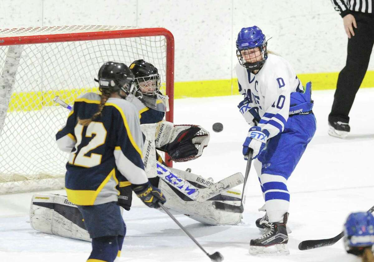 Darien's Corinne Bevill (#10), right, goes after a loose puck in the air that Simsbury goalie Tori LaCroix, center, attempted to glove during the girls high school state hockey playoff game between Darien High School and Simsbury High School at Terry Conners Ice Rink in Stamford, Conn., Saturday, March 3, 2018. LaCroix was not able to glove the puck which led to a scramble in front of the net and an eventual goal for Bevill.