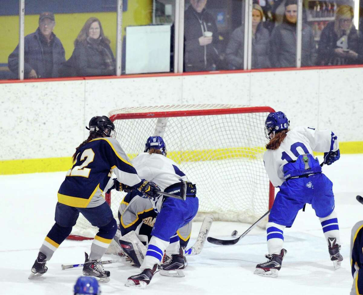 Darien's Corinne Bevill (#10), right, goes after a loose puck in the crease of Simsbury goalie Tori LaCroix that Bevill was able to get to first and put in the net for a second period Darien goal during the girls high school state hockey playoff game between Darien High School and Simsbury High School at Terry Conners Ice Rink in Stamford, Conn., Saturday, March 3, 2018.