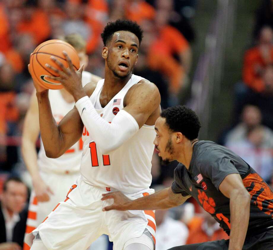 Syracuse's Oshae Brissett, left, looks to pass the ball as Clemson's Marcquise Reed, right, guards during the first half of an NCAA college basketball game in Syracuse, N.Y., Saturday, March 3, 2018. (AP Photo/Nick Lisi) Photo: Nick Lisi / FR171024 AP