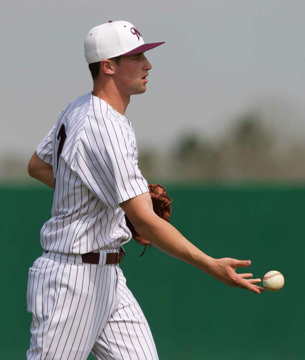 Magnolia starting pitcher Adam Kloffenstein tosses the ball to first baseman Seth Wehunt for an out in the second inning of a high school baseball game against Coppell during the Montgomery-Brenham Tournament, Saturday, March 3, 2018, in Montgomery.