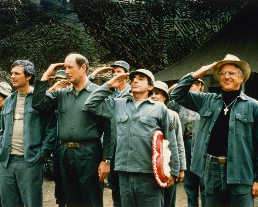 Alan Alda, US actor, David Ogden Stiers, US actor, Jamie Farr, US actor, and William Christopher, US actor, saluting in a publicity still issued for the US television series 'M*A*S*H', USA, circa 1975. The medical comedy starred Alda as 'Captain Benjamin Franklin 'Hawkeye' Pierce, Ogden Stiers as 'Charles Emerson Winchester III', Farr as 'Maxwell Klinger', and Christopher as 'Father Mulcahy'. (Photo by Silver Screen Collection/Getty Images)
