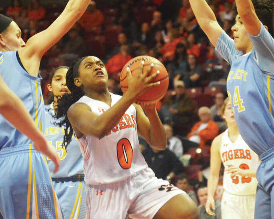 Edwardsville sophomore Quierra Love (middle) goes up for a shot between Maine West defenders during the third-place game in the Class 4A girls basketball state tournament at Redbird Arena on Saturday night in Normal. The Tigers lost to finish at 30-2 in fourth place. Photo: Matthew Kamp / For The Telegraph