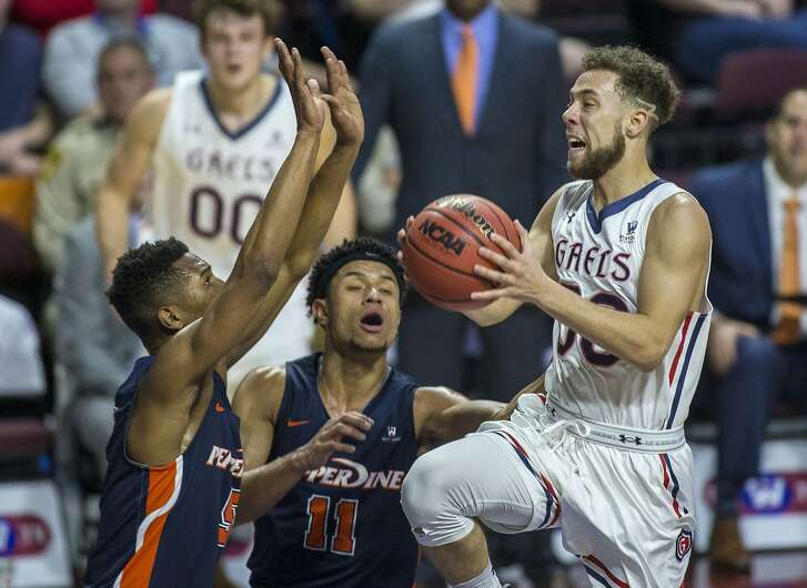 Saint Mary's Jordan Ford (30) jumps up while looking for a possible shot over Pepperdine's Trae Berhow (11) and Jade' Smith (5) during the first half of an NCAA college basketball game in the quarterfinals of the West Coast Conference men's tournament Saturday, March 3, 2018, in Las Vegas. (AP Photo/L.E. Baskow)