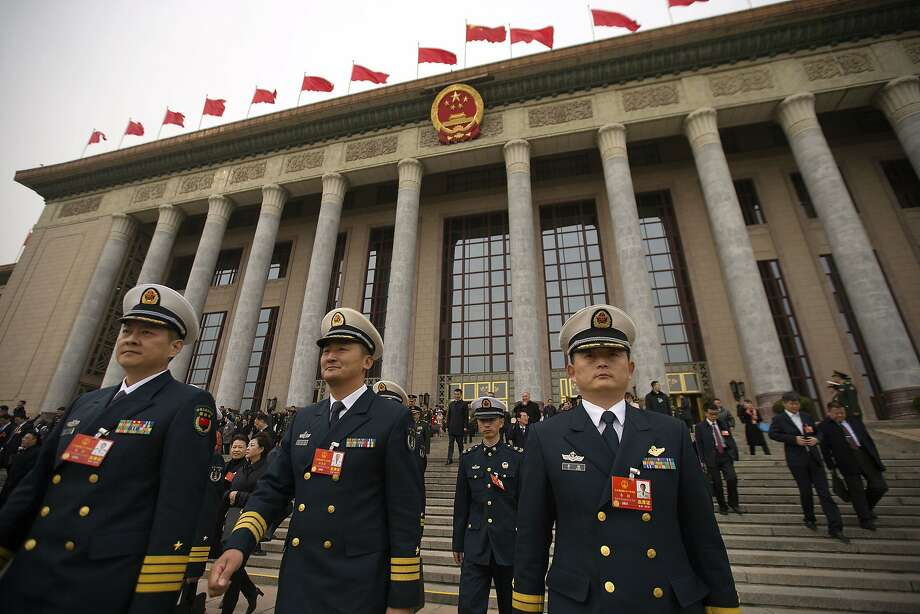 Military officers depart the Great Hall of the People in Beijing. The National People's Congress is expected to approve changes that will allow President Xi Jinping to rule indefinitely. Photo: Mark Schiefelbein, Associated Press