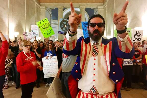FILE - In this March 1, 2018 file photo, Parry Casto, a fifth grade teacher at the Explorer Academy in Huntington, W.Va., dressed in an Uncle Sam costume leads hundreds of teachers in chants outside the state Senate chambers at the Capitol in Charleston, W.Va  The strike rolled into its second weekend with the state Senate planning to meet Saturday, March 3 after declining to take a vote on whether the teachers will get the 5 percent pay raise negotiated by Gov. Jim Justice and union leaders.  (AP Photo/John Raby)