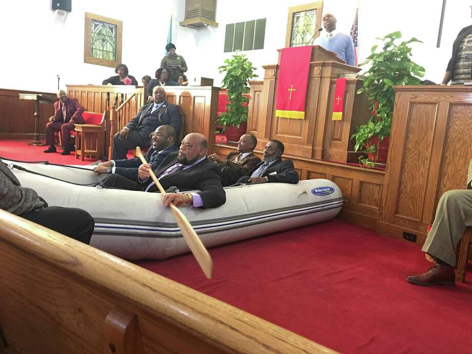 Pastor Kevin Hardy used an inflatable rowboat to illustrate a sermon at St. Matthew's Unison Free Will Baptist Church. In the boat, from left, are Maurice Cummings, Roderick Younger, James Harrell and William Hemby. Photo: Contributed Photo / Lillian Vinston
