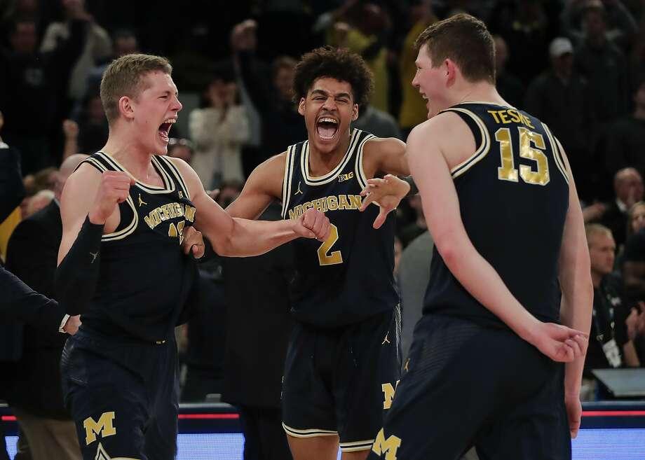 From left, Michigan's Moritz Wagner, Jordan Poole and Jon Teske celebrate. Photo: Julie Jacobson, Associated Press