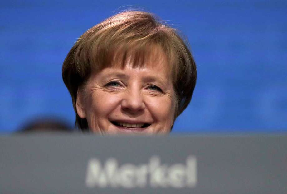 FILE - In this Feb. 26, 2018 file photo German Chancellor and party chairwoman Angela Merkel smiles at the party convention of the Christian Democratic Union CDU in Berlin. The members of the Social Democratic party voted for a coalition agreement with Merkel's party paving the way for Merkel's fourth term as German Chancellor.  (AP Photo/Markus Schreiber, file) Photo: Markus Schreiber / Copyright 2018 The Associated Press. All rights reserved.