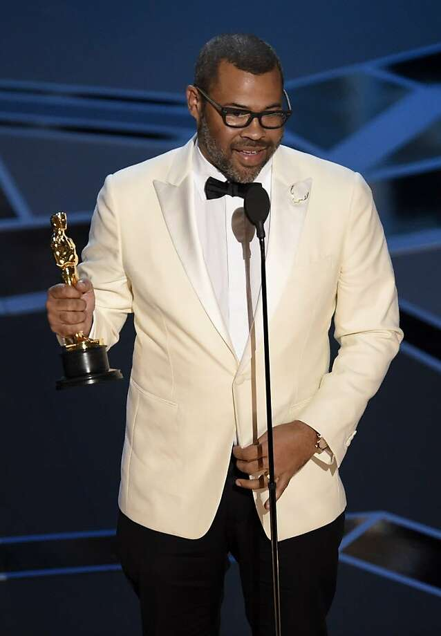 """Jordan Peele accepts the award for best original screenplay for """"Get Out"""" at the Oscars on Sunday, March 4, 2018, at the Dolby Theatre in Los Angeles. (Photo by Chris Pizzello/Invision/AP) Photo: Chris Pizzello, Associated Press"""
