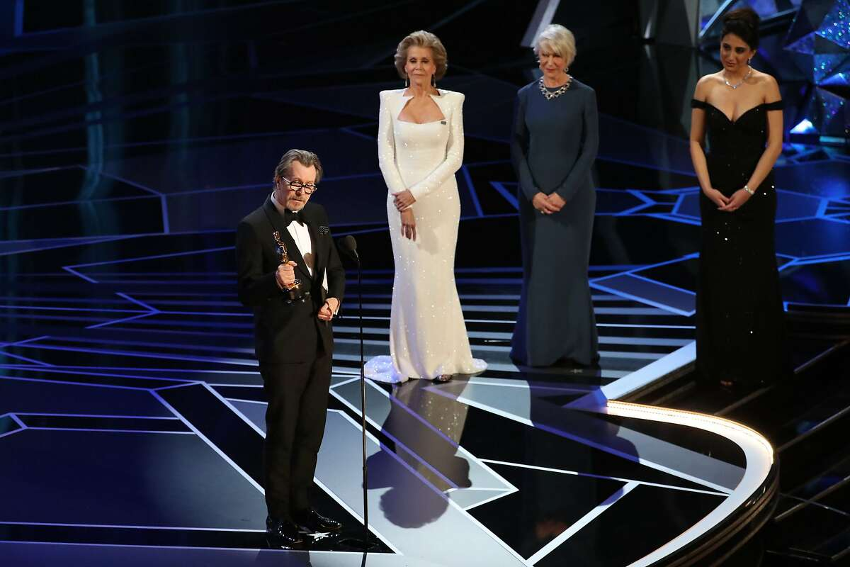"""Gary Oldman accepts the Oscar for best actor in a leading role for """"Darkest Hour"""" during the 90th Academy Awards at the Dolby Theater in Los Angeles, March 4, 2018. From second right, Hellen Mirren and Jane Fonda presented the award. (Patrick T. Fallon/The New York Times)"""