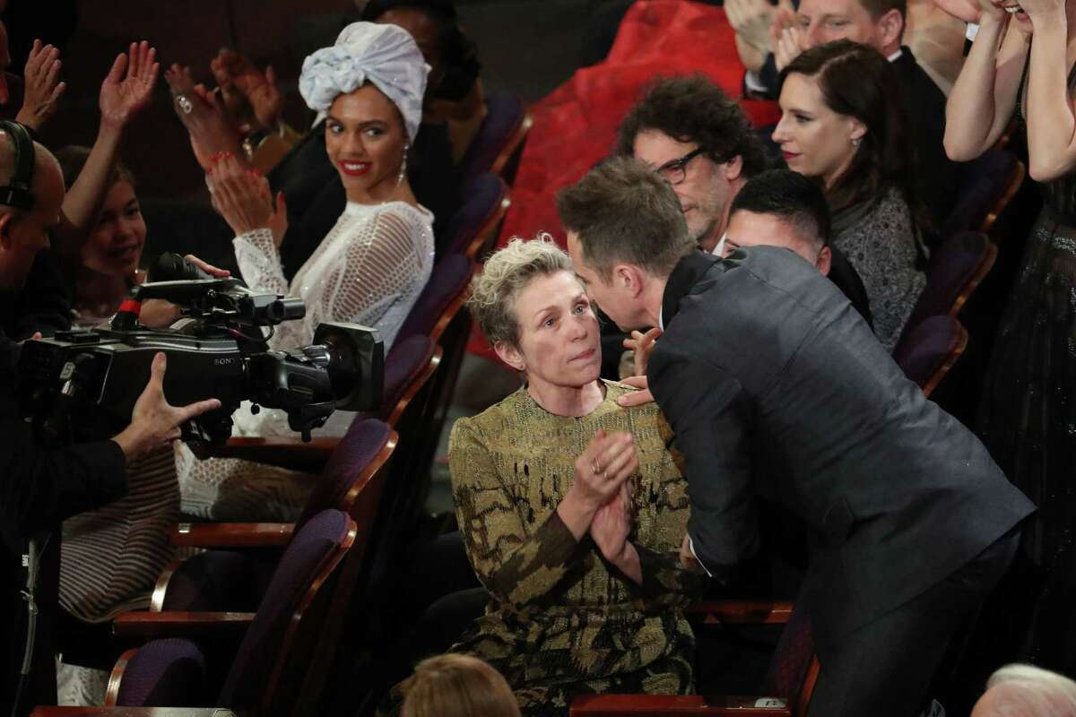 Sam Rockwell embraces Frances McDormand as he is announced the winner of best actor in a supporting role for his performance in