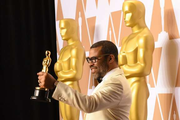 """Director Jordan Peele poses in the press room with the Oscar for Best Original Screenplay for """"Get Out"""" during the 90th Annual Academy Awards on March 4, 2018, in Hollywood, California.  / AFP PHOTO / Robyn BeckROBYN BECK/AFP/Getty Images"""