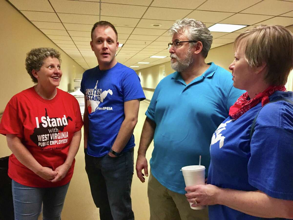 West Virginia teachers, from left, Christi Phillips, Cody Thompson, Sam Brunett and Kristie Skidmore discuss a teachers strike at the state Capitol in Charleston, W.Va. All four teachers said they have second jobs to supplement their incomes.