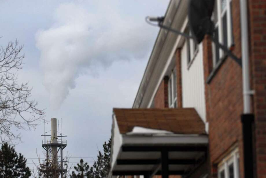 A Norlite stack is near housing authority units in Cohoes. In addition to a $90,000 fine, the polluter will finance a $35,000 environmental project in the city. (Paul Buckowski/Times Union archive) Photo: PAUL BUCKOWSKI