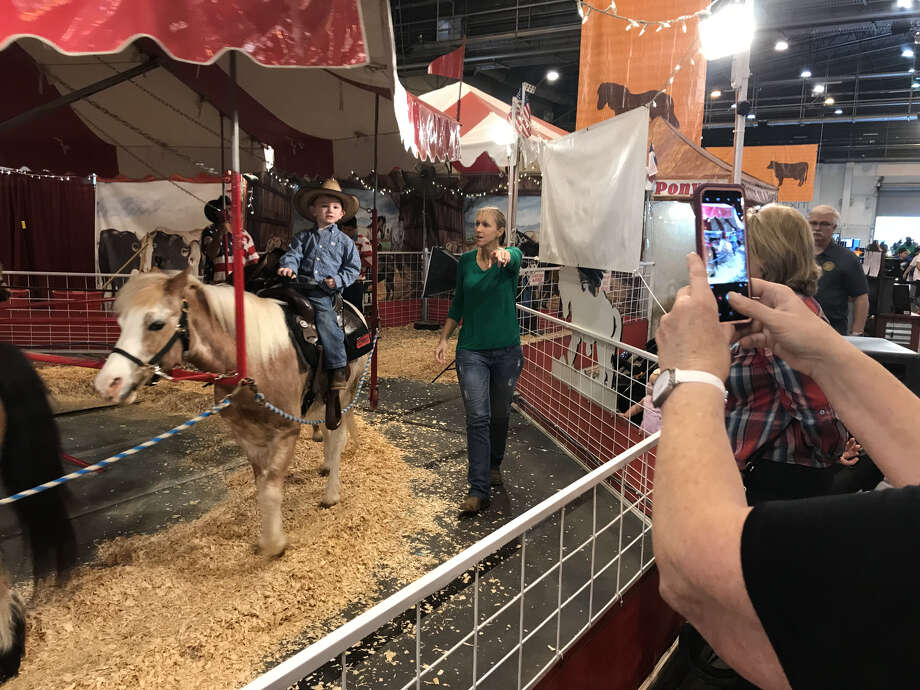 Jodi Colson tries to direct her son, 3-year-old Dylan Colson, to smile so his grandmother can take a cell-phone photo of his pony ride.