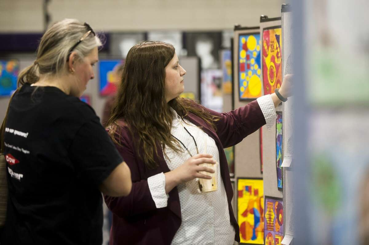 Two women check out works of art by Calvary Baptist Academy students during the school's annual Art and Academic Fair on Friday, March 2, 2018. (Katy Kildee/kkildee@mdn.net)