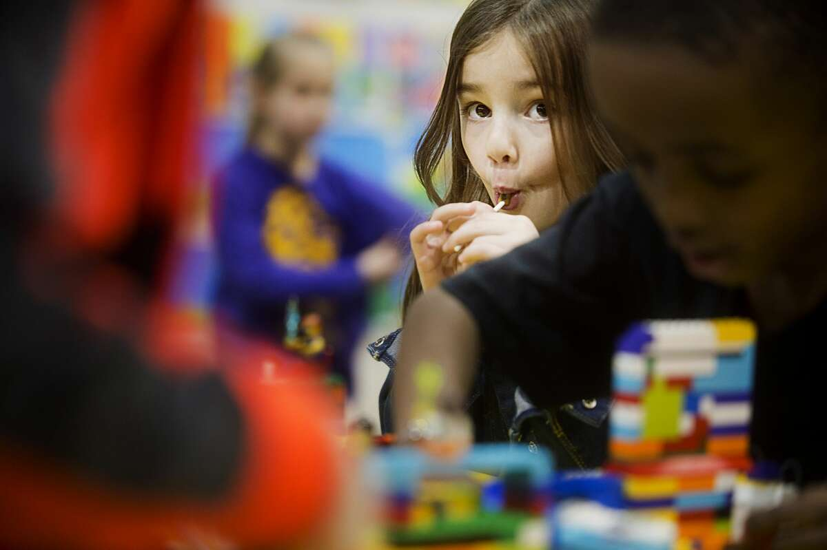 Annie Remy of Midland, 5, enjoys a sucker while watching as other kids work on a robotics project during the school's annual Art and Academic Fair on Friday, March 2, 2018. (Katy Kildee/kkildee@mdn.net)