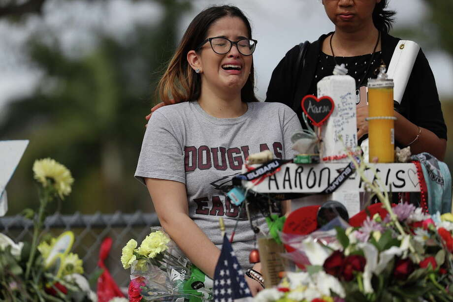 Ariana Gonzalez is over come with emotion as she visits a cross setup for her friend, football coach Aaron Feis, at the memorial in front of Marjory Stoneman Douglas High School in Parkland, Florida. (Photo by Joe Raedle/Getty Images) Photo: Joe Raedle / 2018 Getty Images