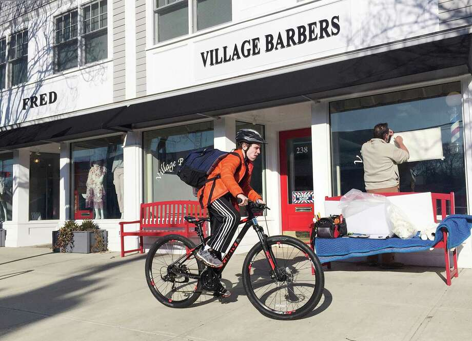 As a boy rides passed on his bicycle, Steven Seifert of Speed Printing and Graphics Company, at right, works on the front window store sign for Village Barbers which is a part of the recently renovated storefronts from 232-260 Sound Beach Avenue in Old Greenwich, Conn., Tuesday, Feb. 27, 2018. The Village Barbers is located at 238 Sound Beach Ave. Photo: Bob Luckey Jr. / Hearst Connecticut Media / Greenwich Time