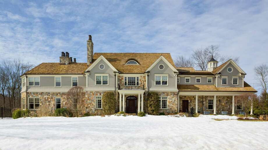 The 13,172-square-foot gray stone and clapboard colonial house at 5 Pritchard Lane sits on a 1.17-acre level property in the Greens Farms neighborhood and features an elevator, in-ground pool and two wine cellars. / Copyright: Barry A. Hyman, 2015