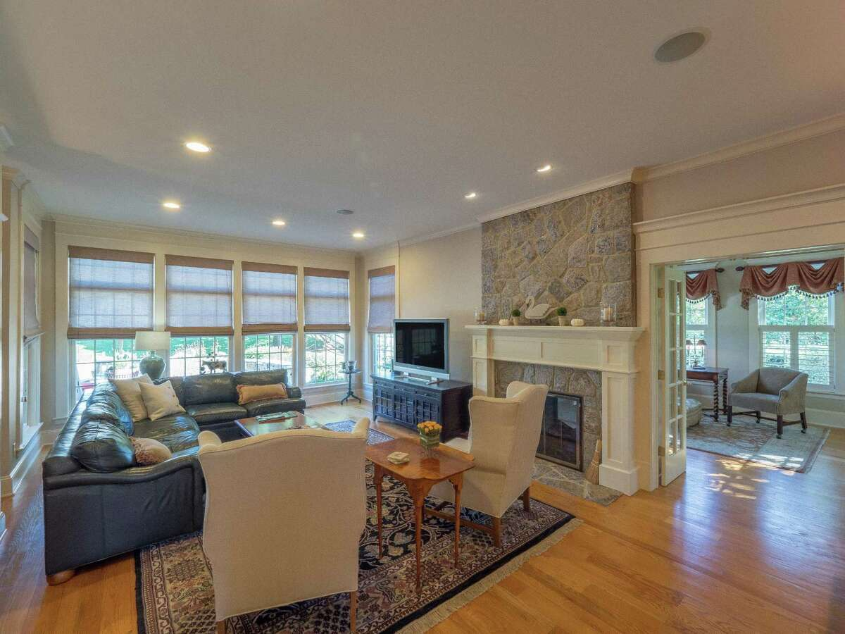 Step down from the kitchen into the family room, which has a double-sided floor-to-ceiling stone fireplace, a wet bar with a long granite counter, and French doors into the sitting or reading room.