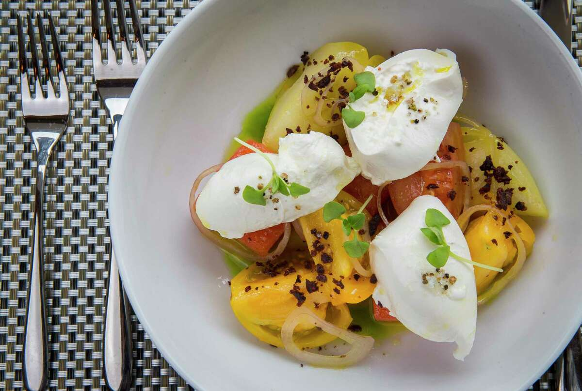 Burrata and heirloom tomatoes with watermelon, apple cider dressing and basil at the Fig & Olive restaurant, Galleria.