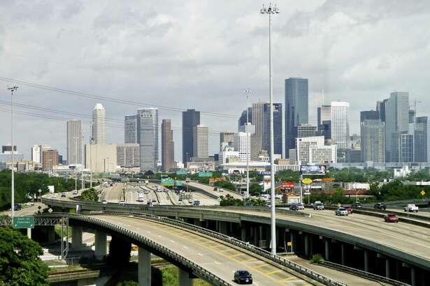 Cars travel along a highway with the skyline of downtown Houston in the background.