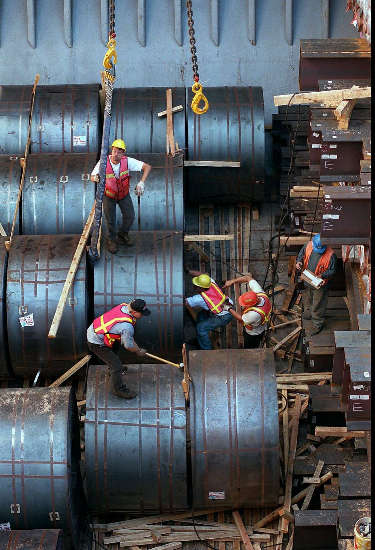 Longshore workers unloading unprocessed steel. On Monday, President Trump said he would press forward with tariffs on imported steel and aluminum.