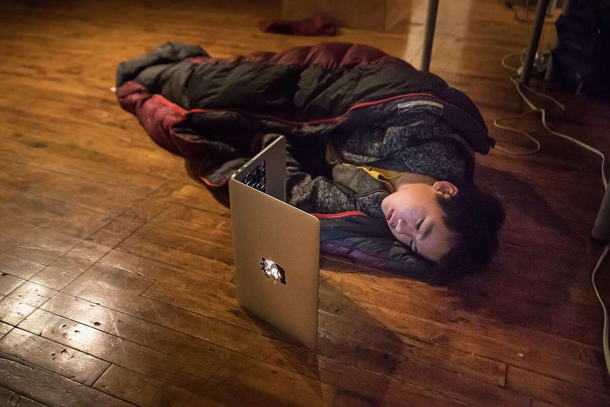 Oliver Ni sets up in his sleeping bag at San Francisco'?s first hackathon for high schoolers on Saturday, March 3, 2018 in San Francisco, Calif.