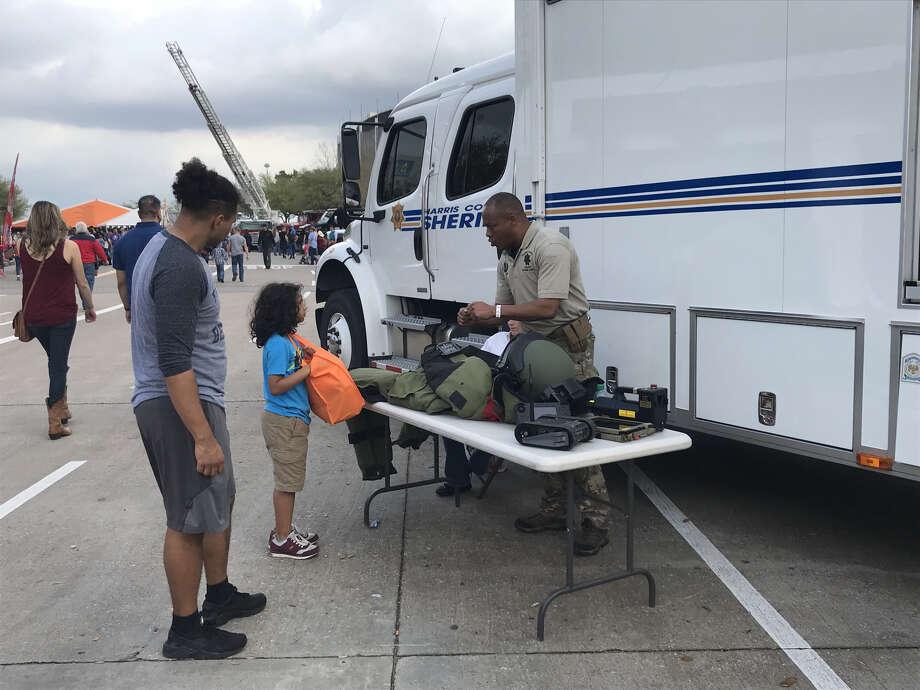 Lamar Ming, a Harris County Sheriff's Office bomb technician, explains his protective gear to a child Monday on First Responders Day at RodeoHouston.