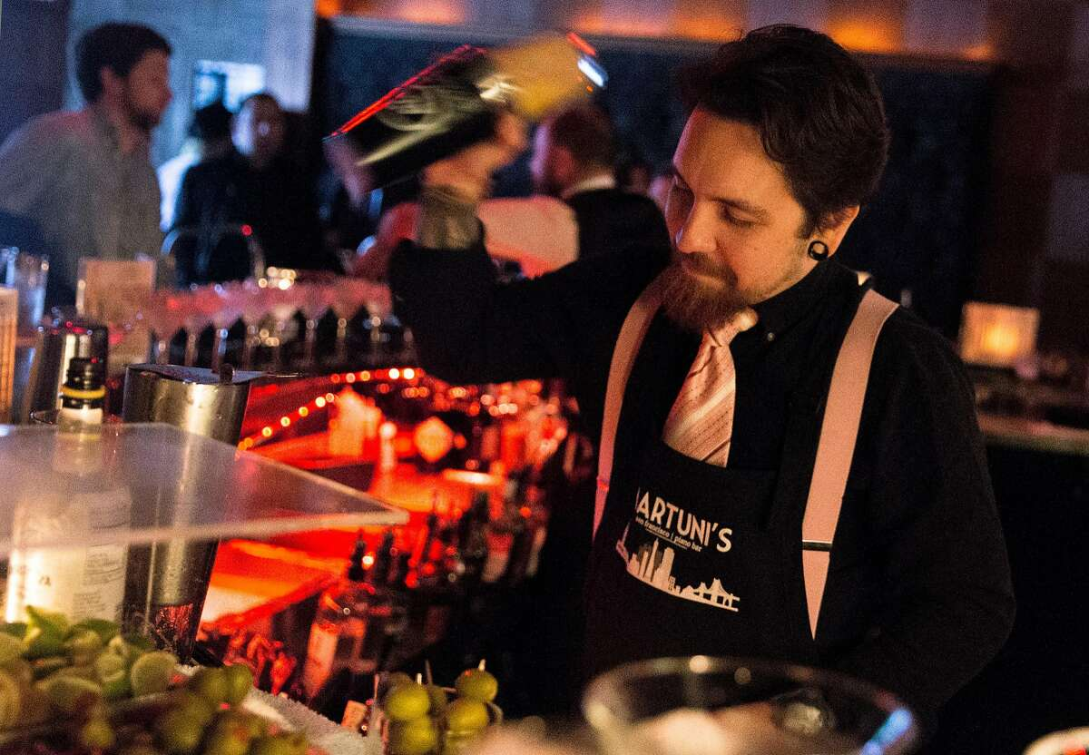 Bartender Vlad Korishev prepares drinks for customers at Martuni's Friday, March 2, 2018 in San Francisco, Calif.